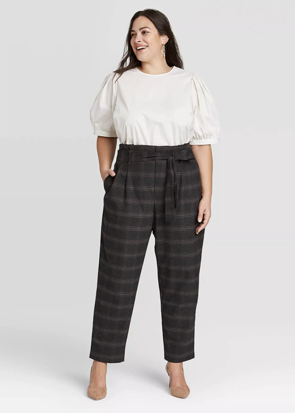 A plus-size model wearing a pair of black plaid pants.