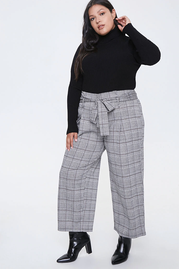 A plus-size model wearing a pair of gray, wide-leg plaid pants.