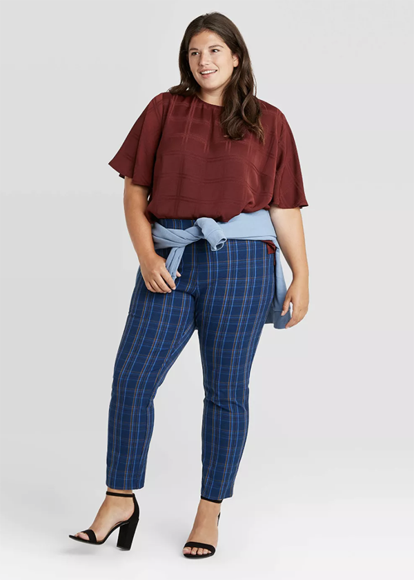 A plus-size model wearing a pair of blue skinny plaid pants.