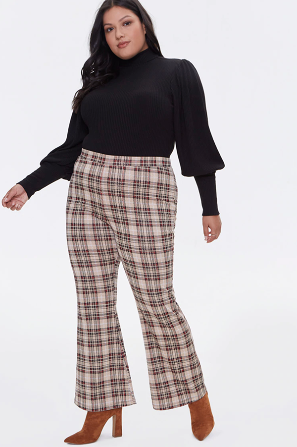 A plus-size model wearing a pair of plaid flare pants.