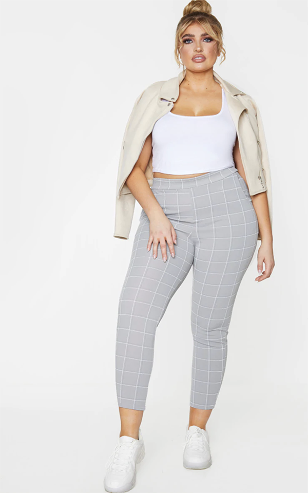 A plus-size model wearing a pair of gray skinny plaid pants.