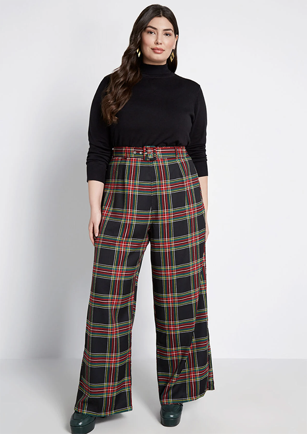 A plus-size model wearing a pair of wide-leg plaid pants.